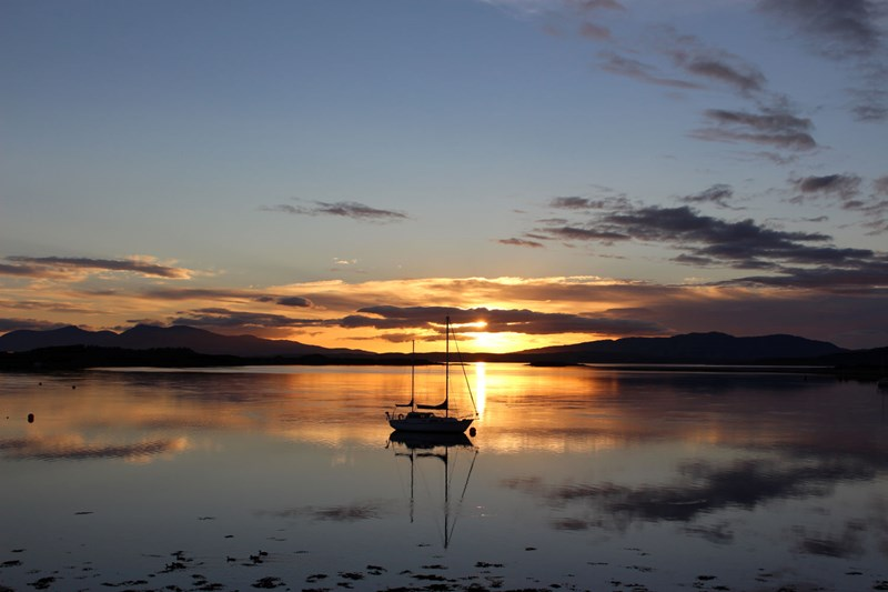View from Connel across to Mull highlighting a yacht in the sunsetaght