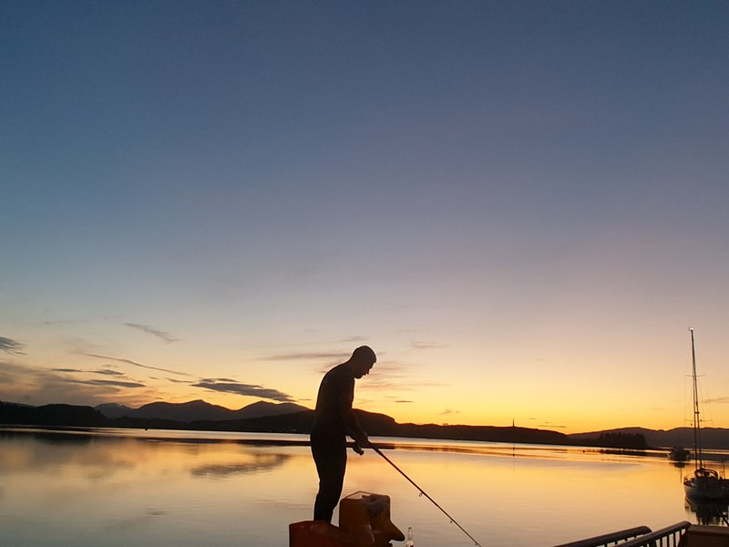 Fisherman in the sunset on Oban's North Pier