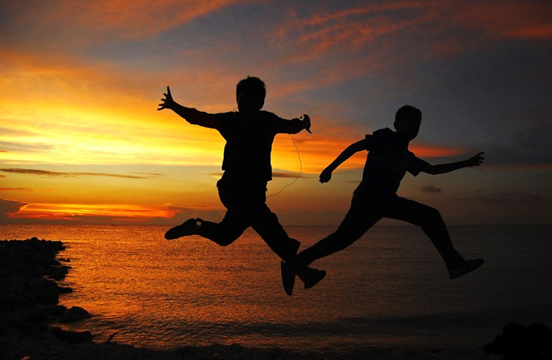 Kids jumping with the sunset in the background