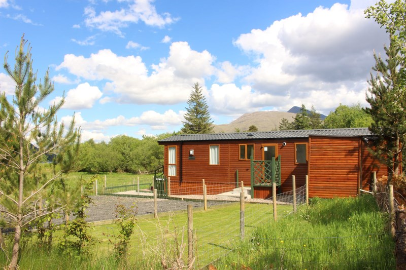 Ben View from the side, showing side garden, patio, utility shed, parking, blue skies and Ben Cruachan in the background