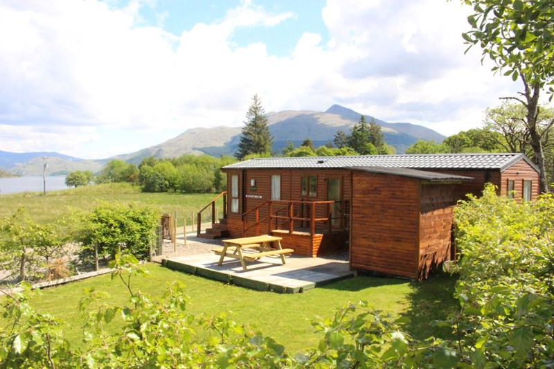 Mountain View from the side, showing side garden, patio and furniture, parking, utility shed, blue skies and Ben Cruachan in the background