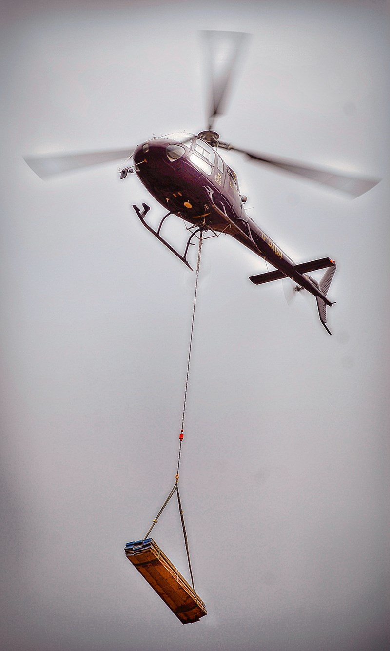 Helicopter, in flight, with slung load of materials.